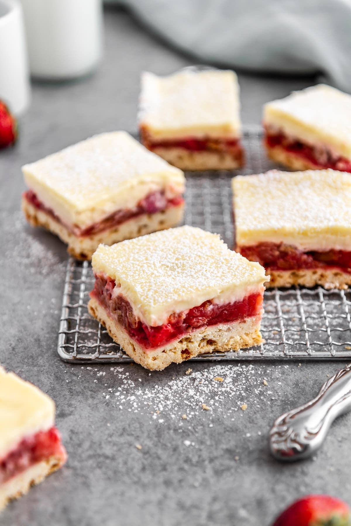 strawberry rhubarb cheesecake bars on a cooling rack