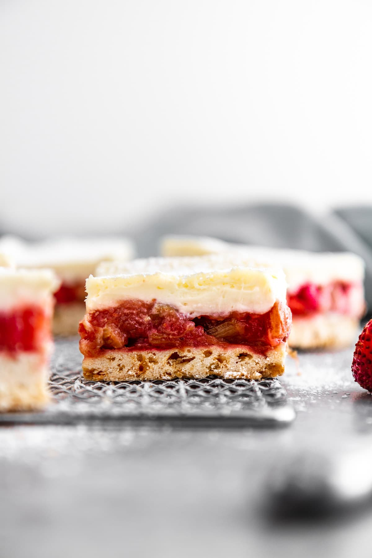 close up of a strawberry rhubarb cheesecake bar