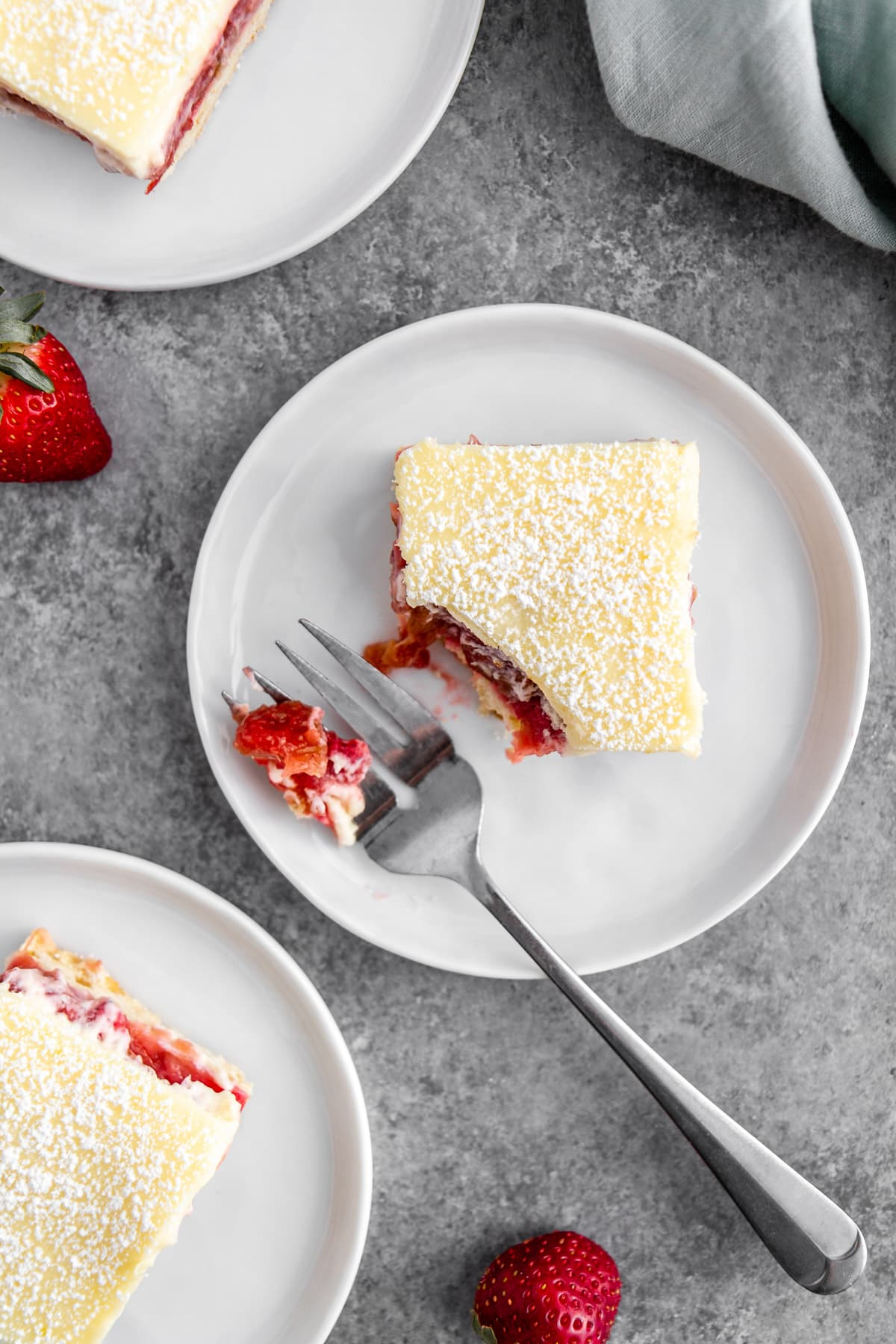 strawberry rhubarb cheesecake bars on plates with a fork