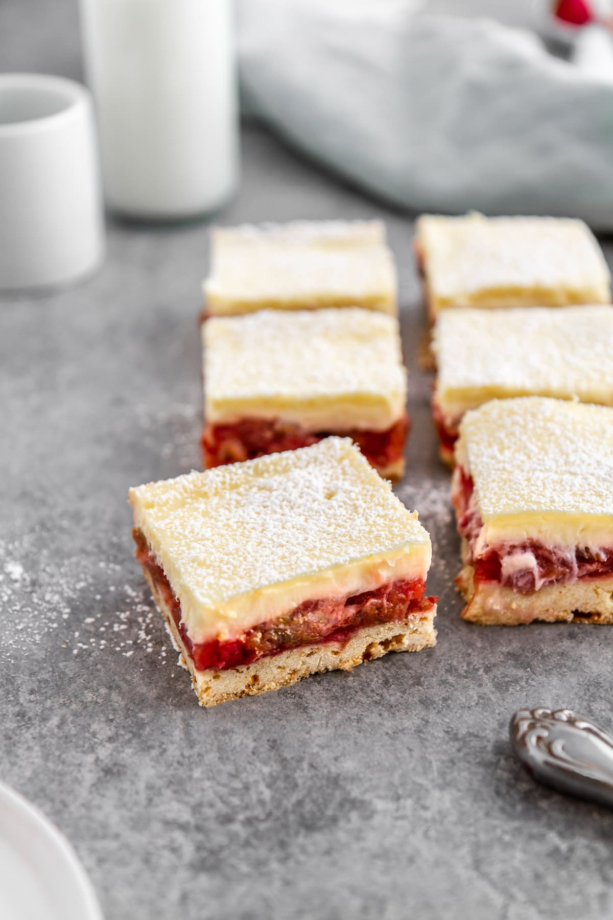 strawberry rhubarb cheesecake bars on a surface
