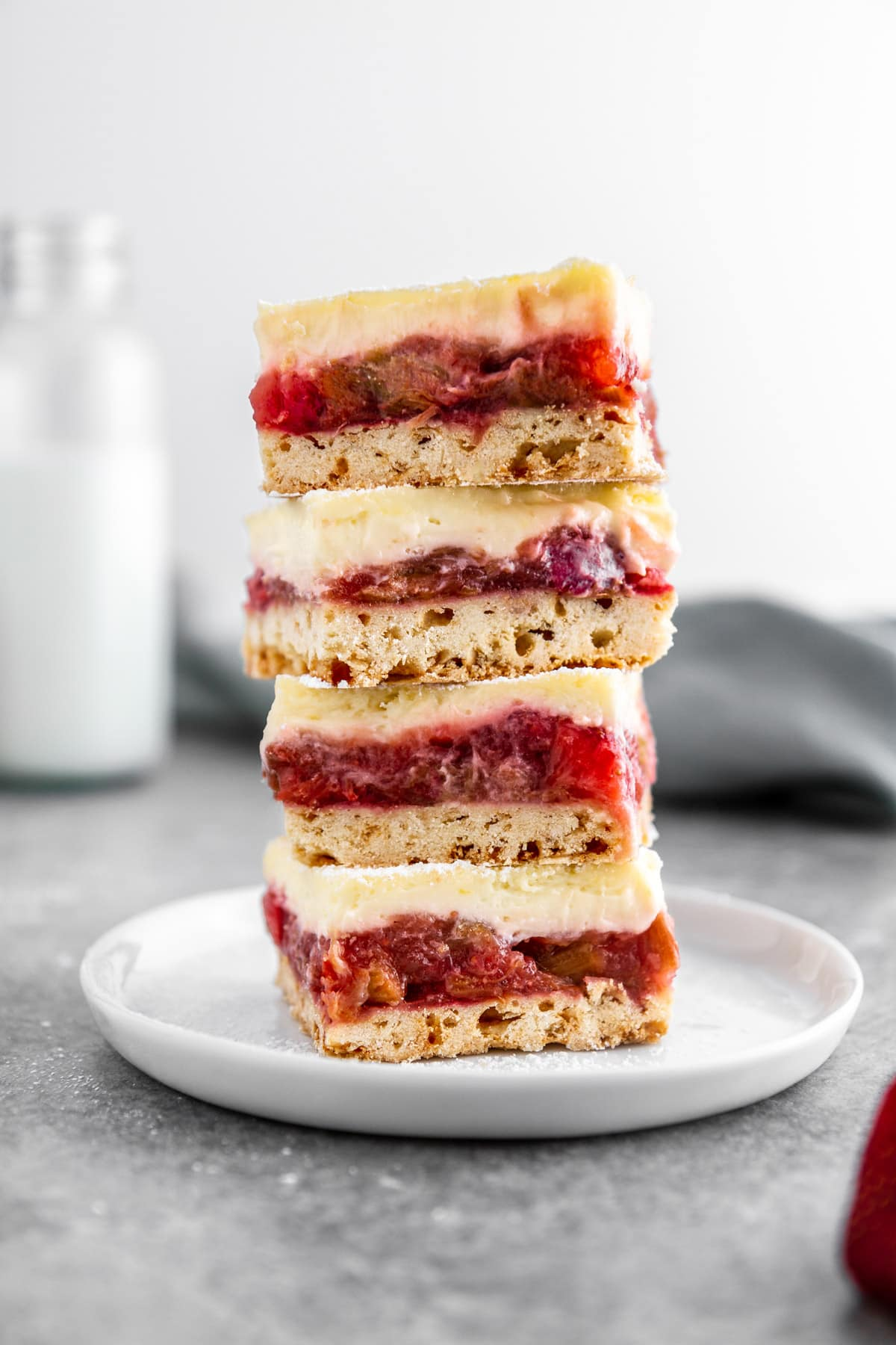 a stack of strawberry rhubarb cheesecake bars on a plate
