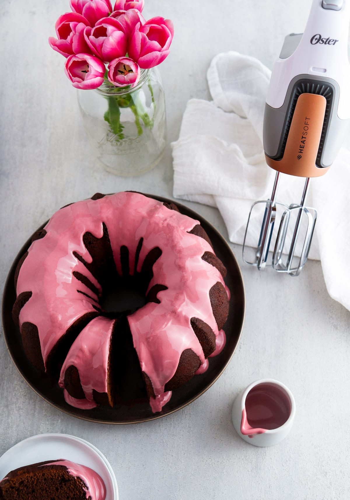 a chocolate bundt cake with ruby chocolate glaze on a plate with a hand mixer and flowers next to it