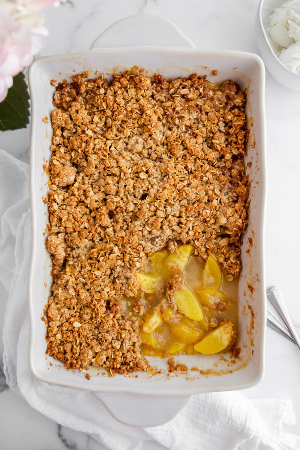 peach crisp with a crunchy oat topping in a baking dish with a scoop taken out