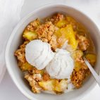 peach crisp in a bowl with vanilla ice cream