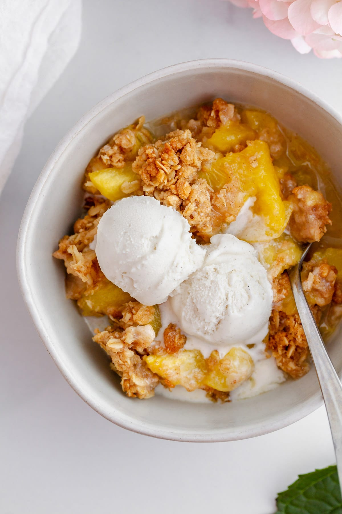 a bowl of peach crisp with a crunchy oat topping and vanilla ice cream on a surface