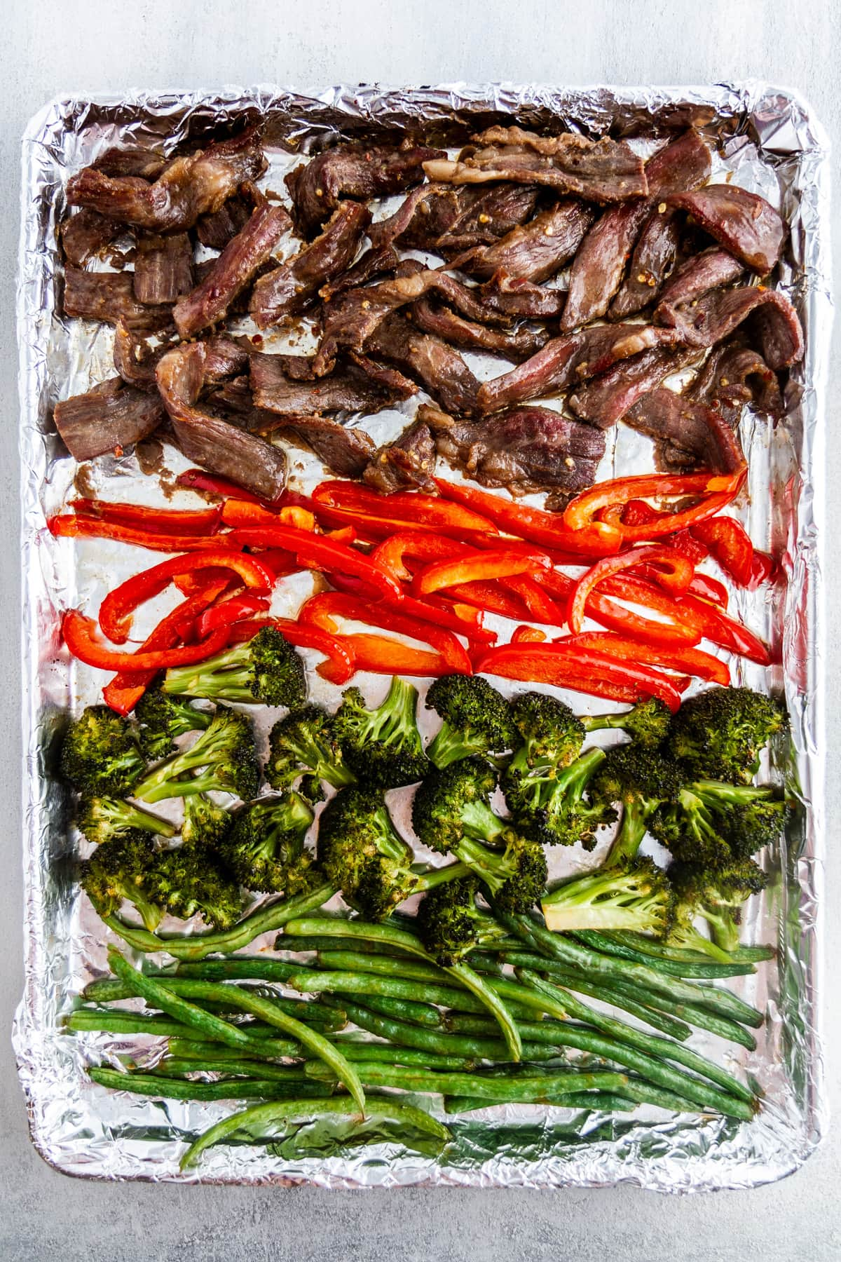mongolian beef and vegetables on a sheet pan