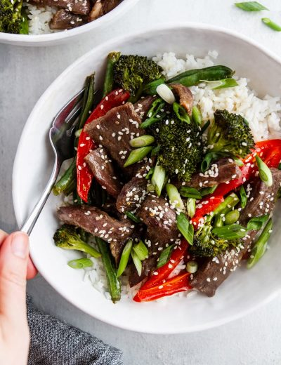 a bowl of sheet pan mongolian beef with a fork in it