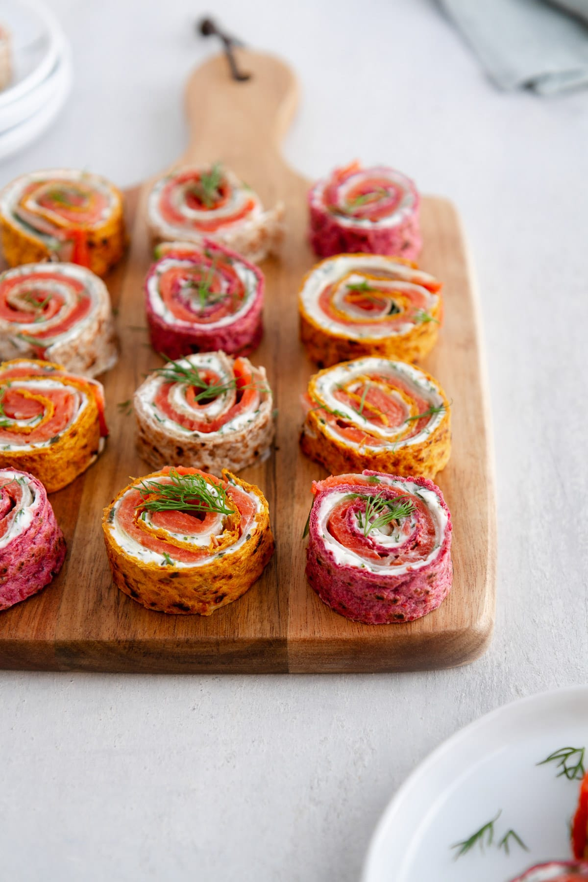 salmon pinwheels on a cutting board