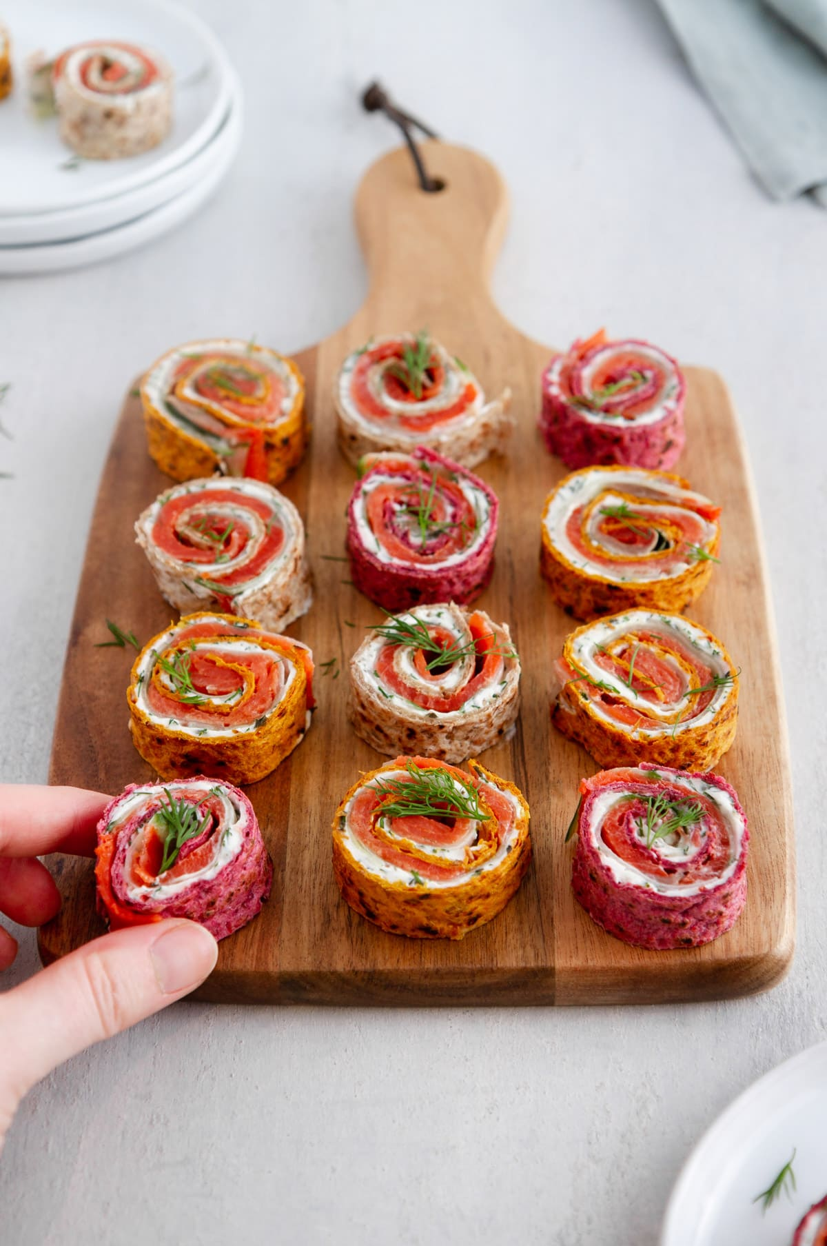 a hand grabbing a salmon pinwheel from a cutting board