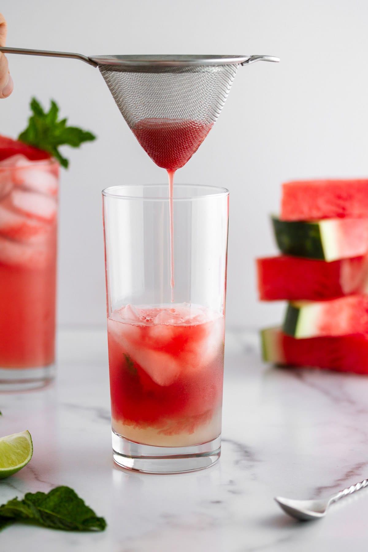 straining watermelon juice into a glass