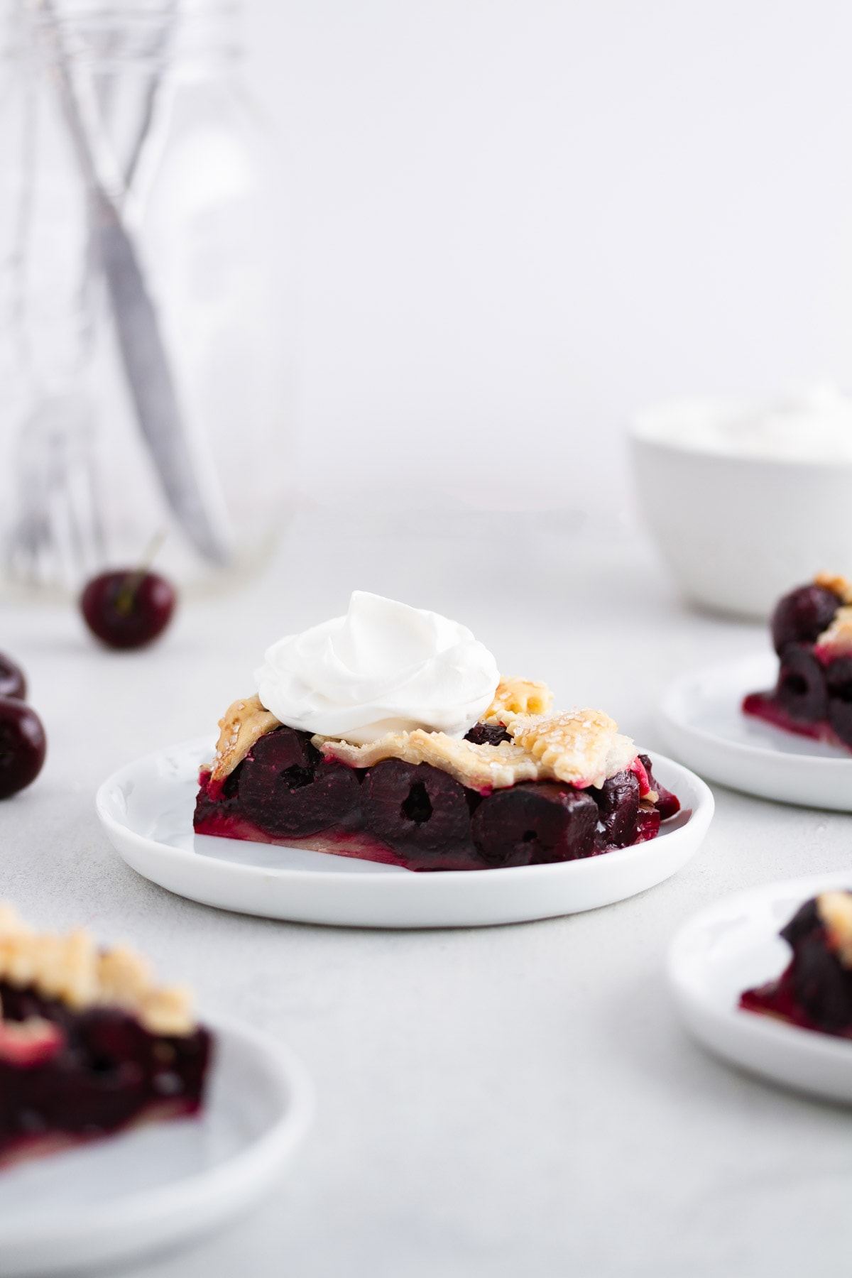 cherry pie bars on plates with whipped cream