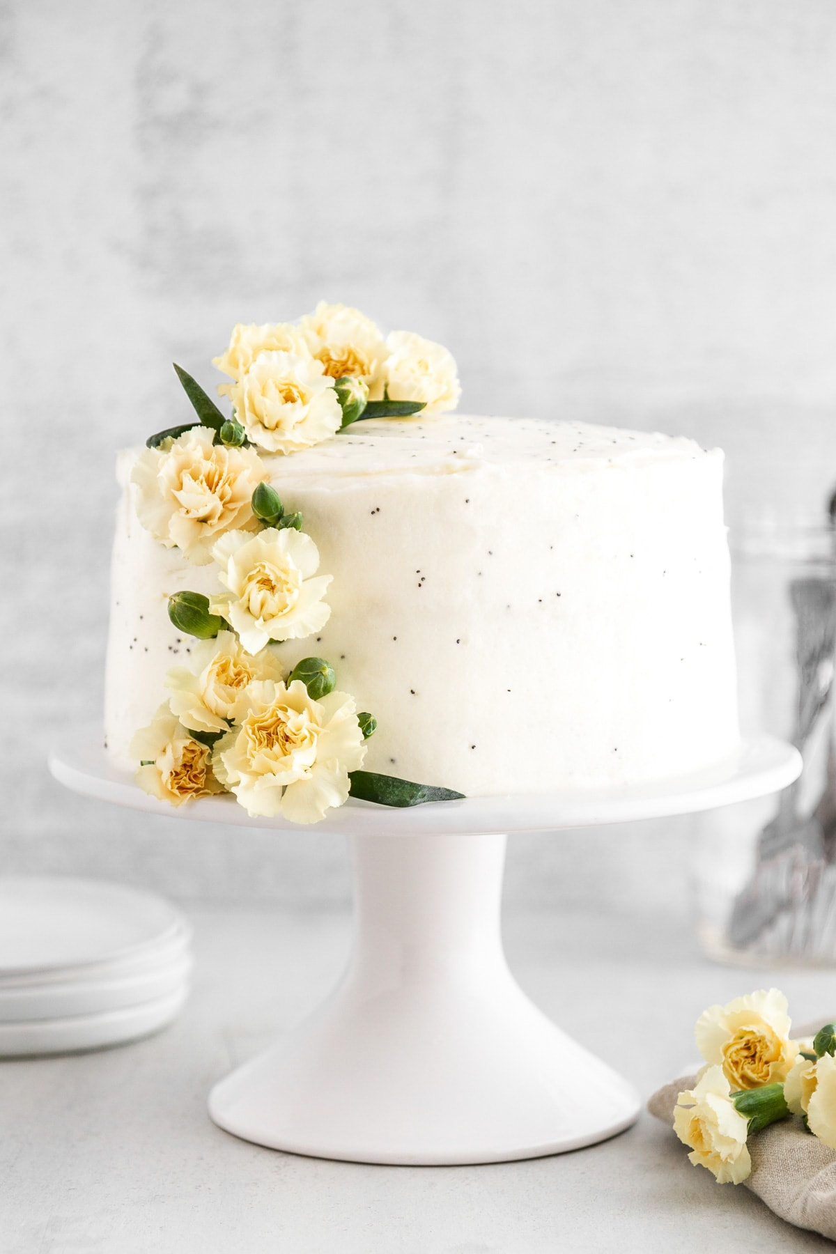 a lemon poppy seed cake on a cake stand