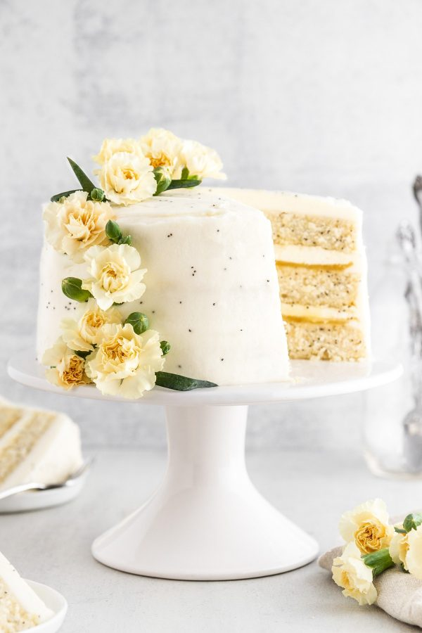 A lemon poppy seed cake on a cake stand with a slice taken out