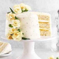 lemon poppy seed cake on a cake stand with a slice taken out