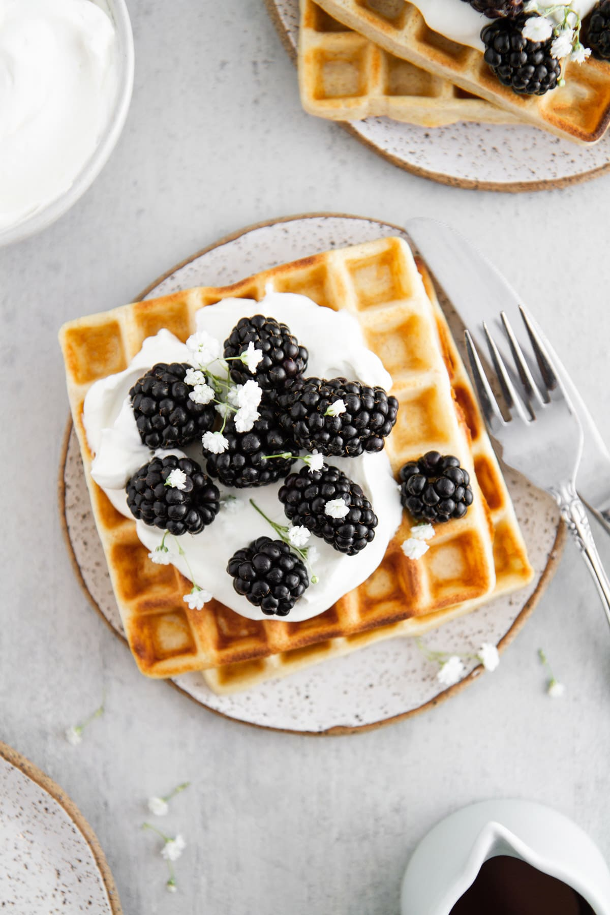 overhead shot of sourdough waffles on a plate with whipped cream and berries