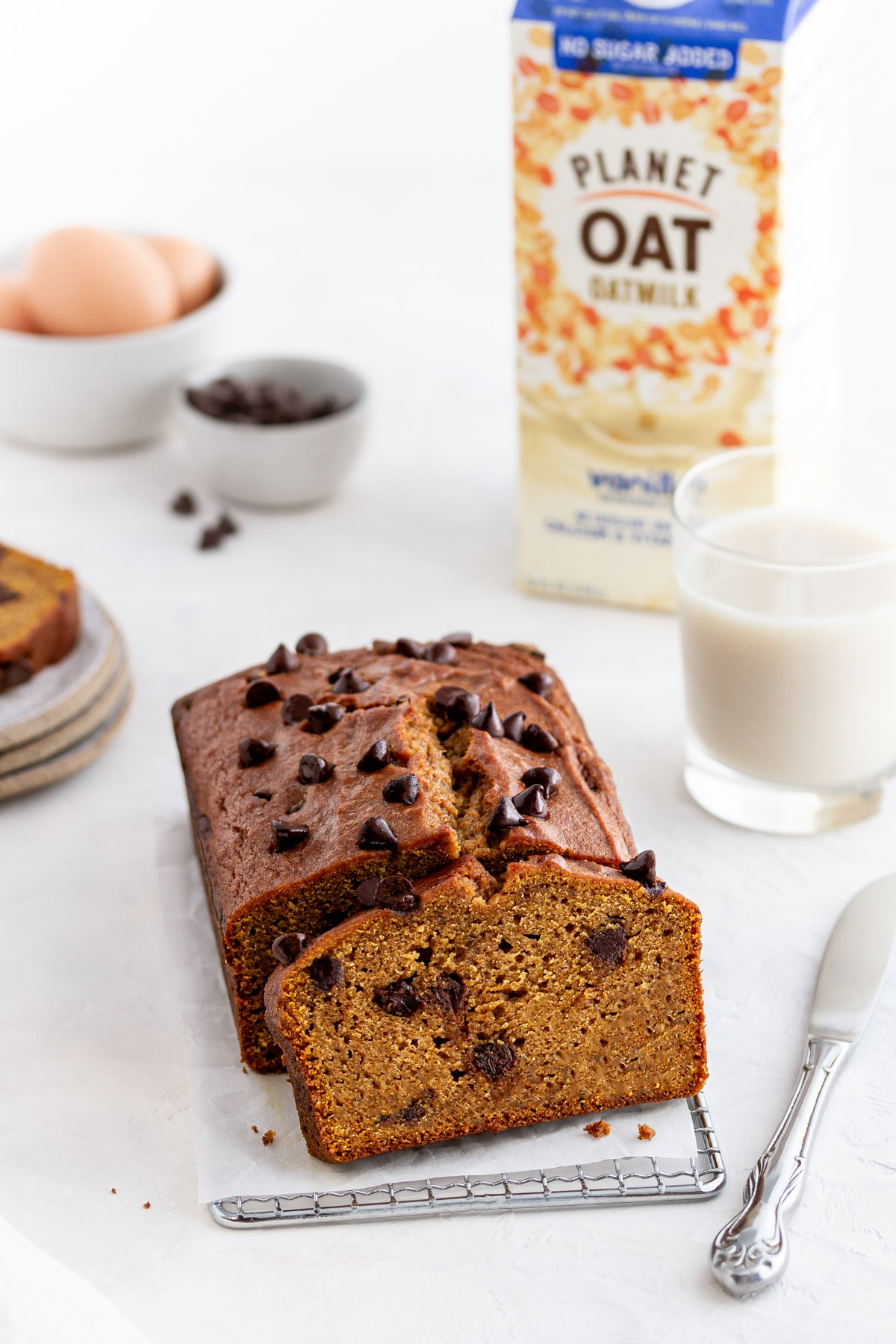 chocolate chip pumpkin bread on a surface with plates and bowls in the background