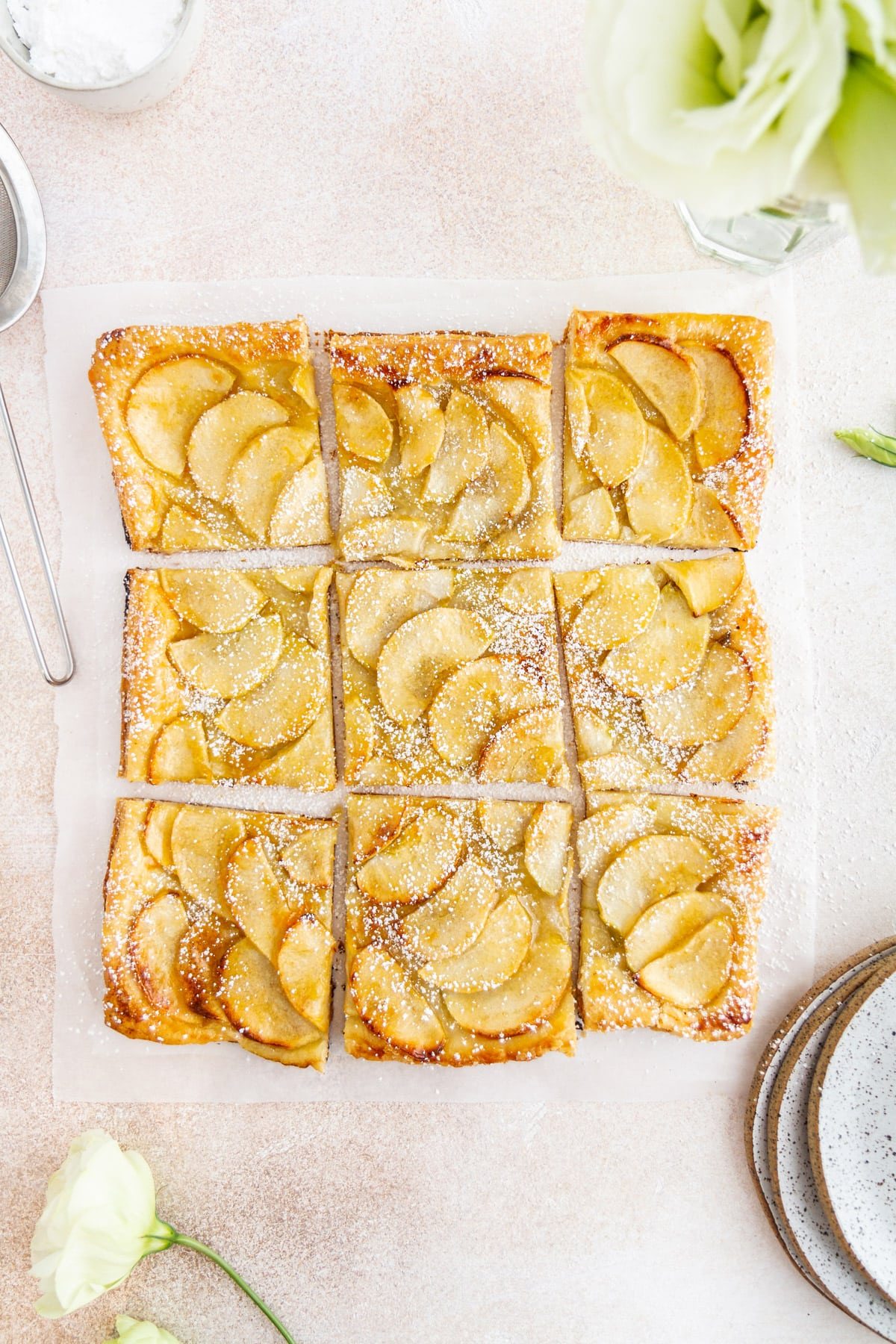 French apple tart cut up on a surface