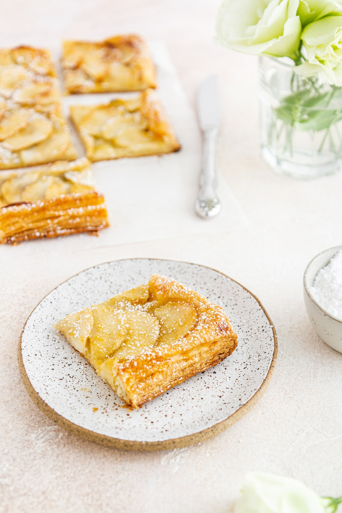 a slice of French apple tart on a plate