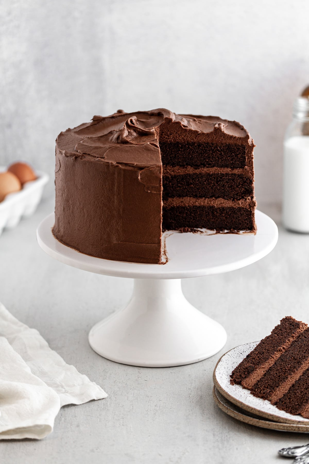 Devil's Food Cake on a cake stand with a slice taken out of it