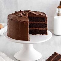 Devil's Food Cake on a cake stand with a slice taken out