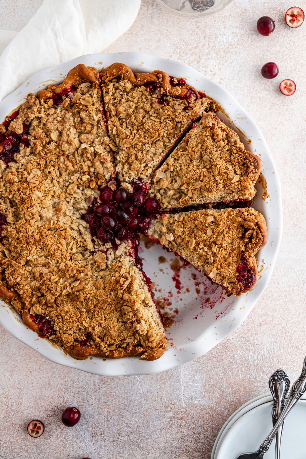 cranberry crumble pie on a surface with a slice taken out of it