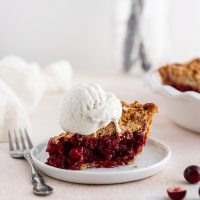 a slice of cranberry crumble pie with ice cream on top