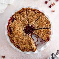 cranberry crumble pie on a surface with a slice taken out