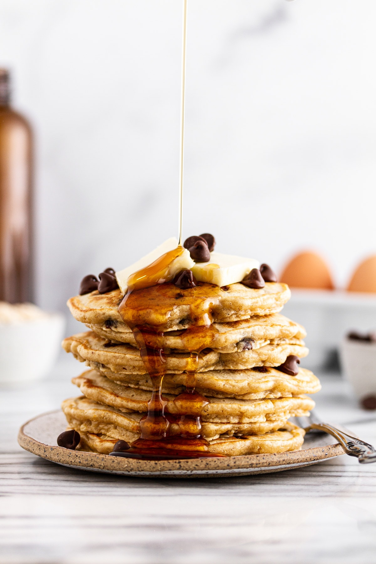syrup pouring onto a stack of oatmeal chocolate chip pancakes