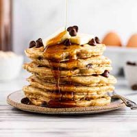 pouring maple syrup on a stack of oatmeal chocolate chip pancakes