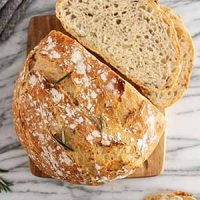 sliced rosemary-garlic no-knead bread on a cutting board