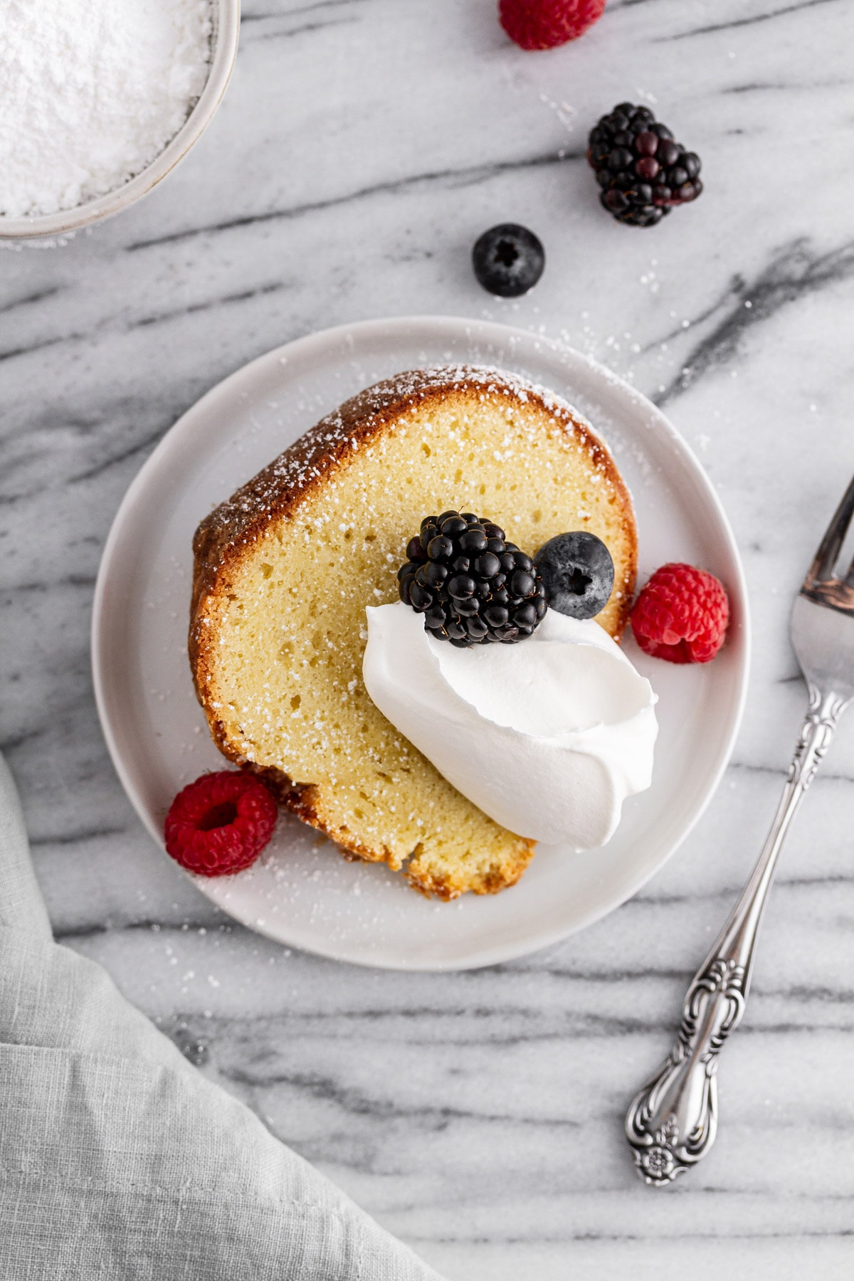 slice of sour cream pound cake on a plate with whipped cream and berries