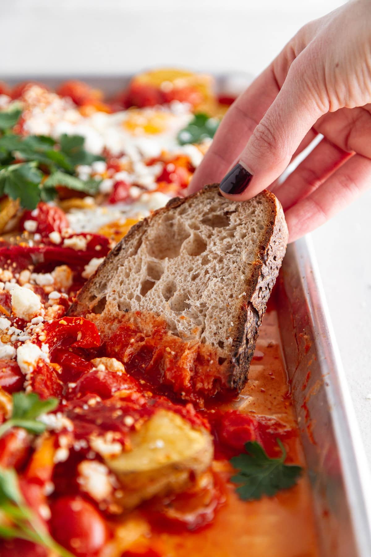 dipping a slice of bread into sheet pan shakshuka