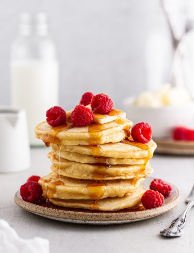 sourdough pancakes on a plate with syrup dripping