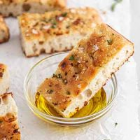 slice of sourdough focaccia dipped into a bowl of olive oil