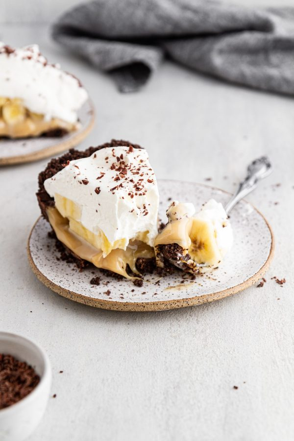 a slice of banoffee pie on a plate with a forkful taken out