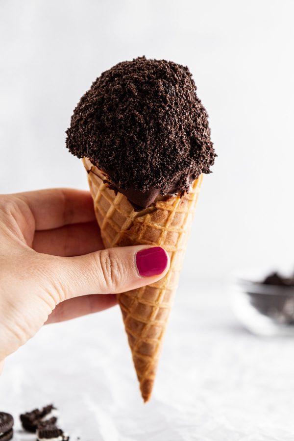 hand holding one cookies and cream ice cream drumstick