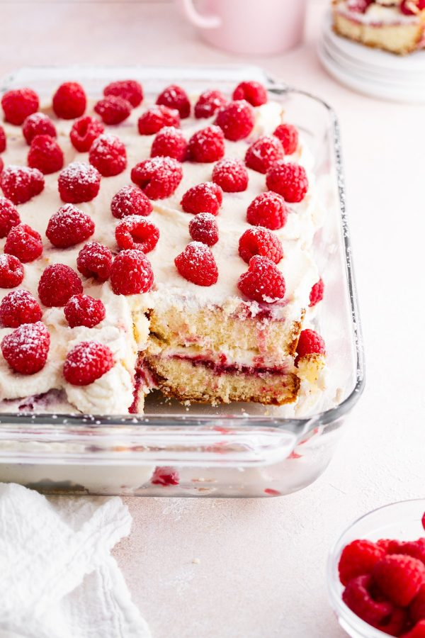 raspberry pound cake tiramisu in a baking dish on a surface with a piece taken out