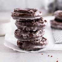 stacked chocolate old-fashioned donuts on parchment paper