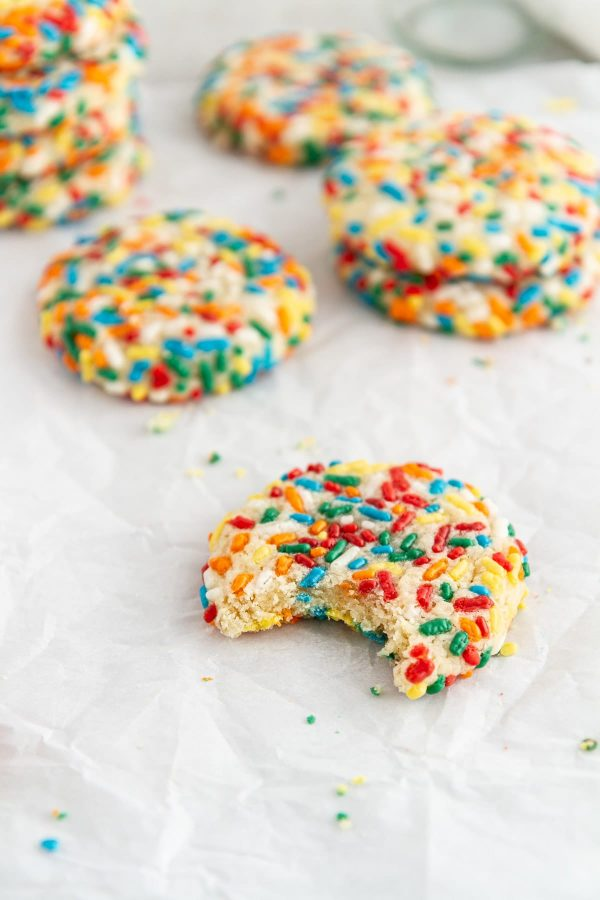 confetti cookies on parchment paper with a bite taken out of one