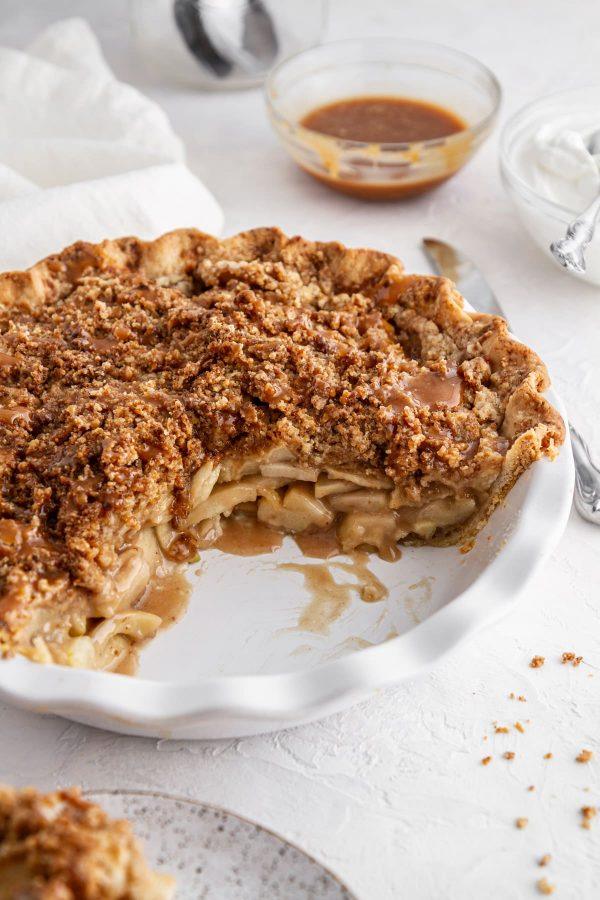 Dutch caramel apple pie in a pie plate with a slice taken out