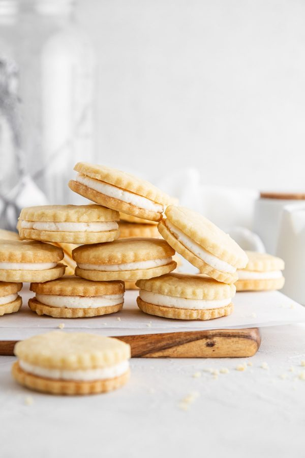 maple cream cookies stacked on a cutting board