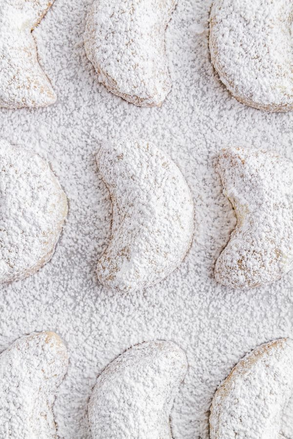 chai-spiced crescent cookies on a sheet of parchment paper