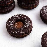 chocolate nutella linzer cookies stacked on a surface