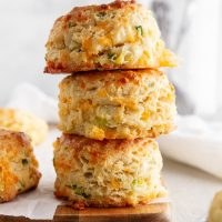stack of cheddar-scallion biscuits on a cutting board