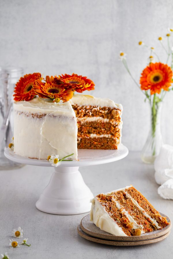 carrot cake on a cake stand with a slice on a plate off to the side