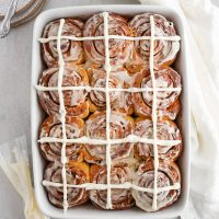 overhead of hot cross cinnamon rolls in a baking pan