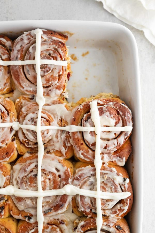 overhead of hot cross cinnamon rolls in a baking pan with one taken out