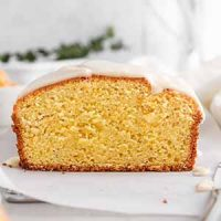sliced iced clementine pound cake on parchment paper