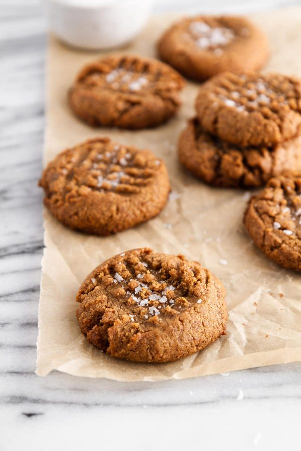flourless almond butter cookies stacked on parchment paper