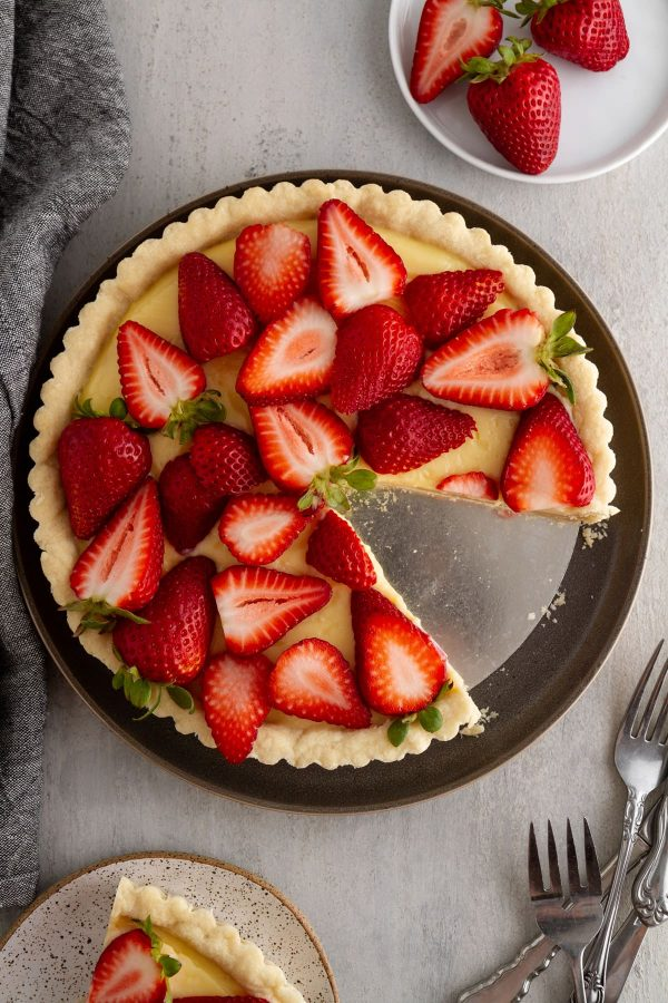 strawberry custard tart on a plate with a slice taken out of it